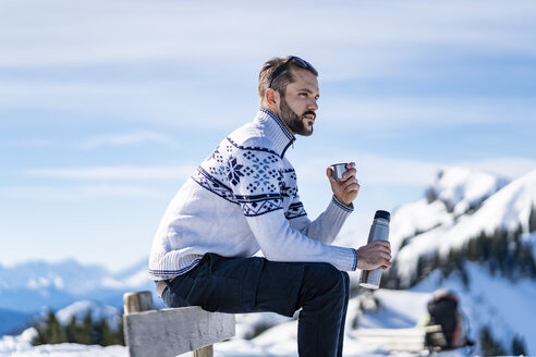 Germany, Bavaria, Brauneck, man sitting on bench in winter in the mountains having a break - DIGF05915
