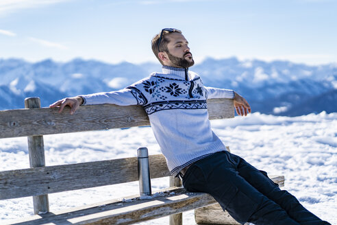 Germany, Bavaria, Brauneck, man sitting on bench in winter in the mountains having a break - DIGF05918