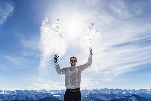 Germany, Bavaria, Brauneck, man in winter playing with snow in the mountains - DIGF05933