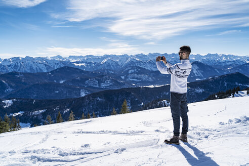 Germany, Bavaria, Brauneck, man in winter in the mountains taking a picture - DIGF05936
