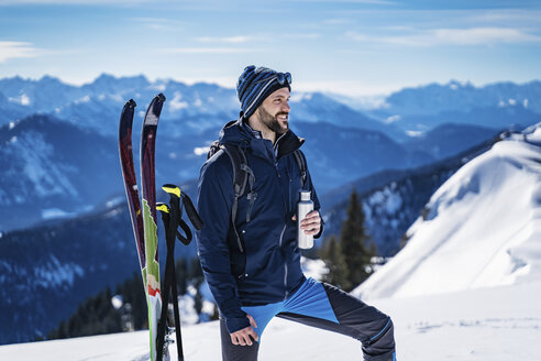 Germany, Bavaria, Brauneck, man on a ski tour in winter in the mountains having a break - DIGF05960
