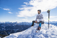 Germany, Bavaria, Brauneck, man in winter sitting on mountaintop - DIGF05969
