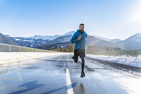 Germany, Bavaria, sportive man running on a road in winter - DIGF05975