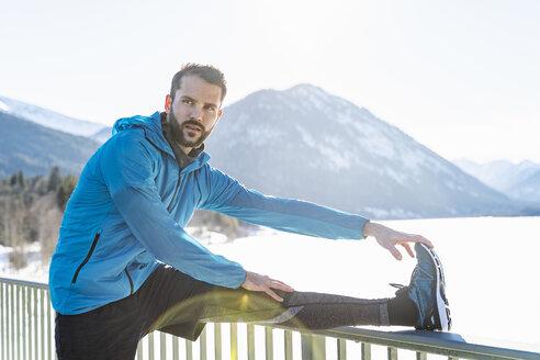 Germany, Bavaria, sportive man stretching in winter on bridge railing - DIGF05978