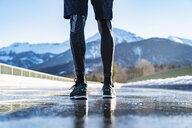 Germany, Bavaria, legs of sportive man standing on a road in winter - DIGF05981