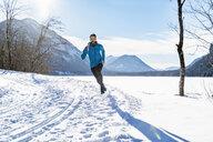 Germany, Bavaria, sportive man running through snow in winter - DIGF05984