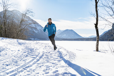 Germany, Bavaria, sportive man running through snow in winter - DIGF05984