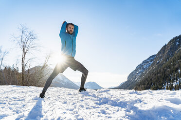 Germany, Bavaria, sportive man stretching in winter - DIGF05990