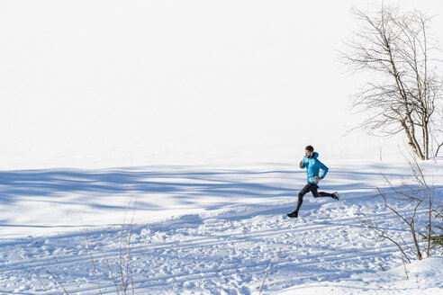 Germany, Bavaria, sportive man running through snow in winter - DIGF05993