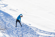 Germany, Bavaria, sportive man stretching in snow in winter - DIGF05996