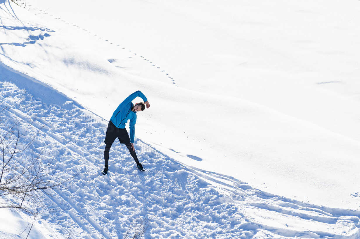Germany, Bavaria, sportive man stretching in snow in winter - DIGF05996 - Daniel Ingold/Westend61