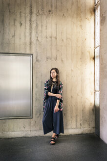 Portrait of fashionable young woman standing in front of concrete wall - DMOF00146