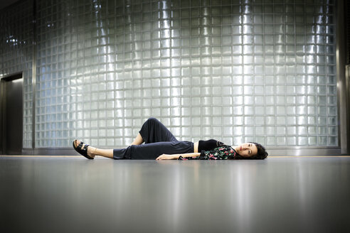 Sad young woman lying on the floor - DMOF00149
