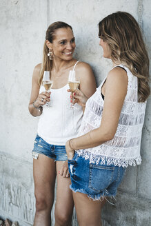 Two best friends drinking champagne outdoors - HMEF00235