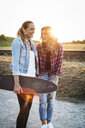 Two laughing friends with longboard at sunset - HMEF00256