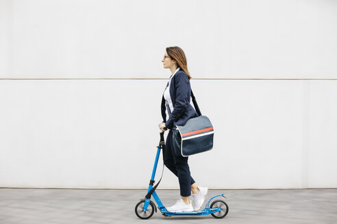 Active businesswoman riding scooter in the city - JRFF02736