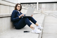 Portrait of businesswoman sitting outdoors on stairs using laptop - JRFF02742