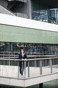 Businesswoman standing outside office building in the city - JRFF02754