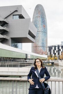 Spain, Barcelona, confident businesswoman standing outside office building in the city - JRFF02757