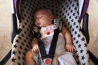 Portrait of little boy sleeping in child safety seat - IGGF00864