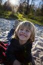 Portrait of laughing little boy lying on blanket outdoors - JLOF00309