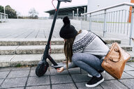Young woman crouching at electric scooter in the city - MGOF03955