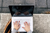 Close-up of woman using laptop outdoors - MGOF03958