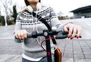 Close-up of young woman with electric scooter in the city - MGOF03961