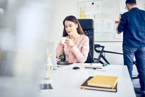 Woman working at desk in office with colleague in background - BSZF00994