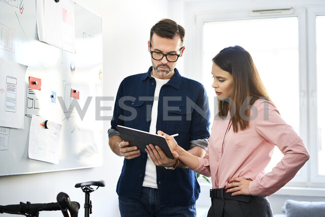 Two colleagues at whiteboard sharing tablet in office - BSZF01000 - Bartek Szewczyk/Westend61