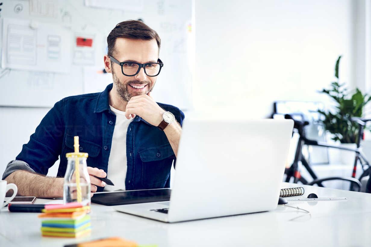 Casual businessman working on laptop at desk in office - BSZF01012 - Bartek Szewczyk/Westend61