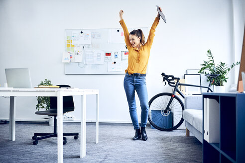 Happy young businesswoman cheering in office - BSZF01027