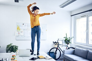 Happy young businesswoman cheering in office - BSZF01030