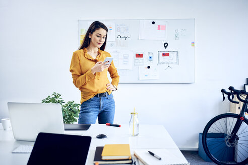 Businesswoman holding smartphone at whiteboard in office - BSZF01039