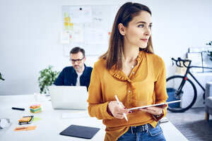 Businesswoman holding tablet in office with colleague in background - BSZF01042