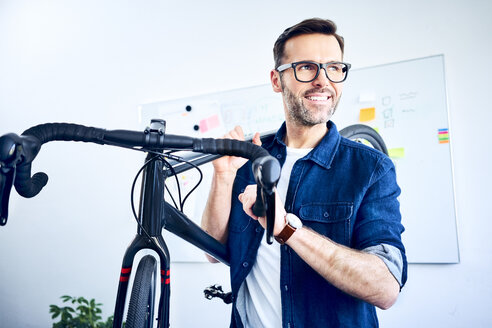 Smiling businessman carrying bicycle in office - BSZF01060