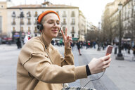 Young woman taking a selfie while listening to music and making peace gesture with her hand - WPEF01365