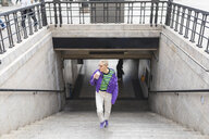 Young woman wearing colorful clothes walking up a staircase in the city - WPEF01371
