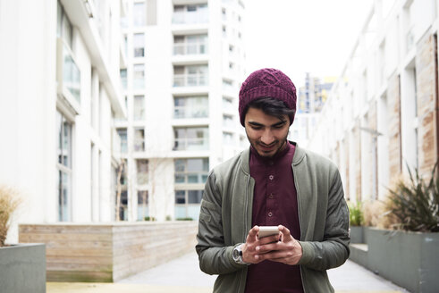 Portrait of cheerful bearded man in purple hat using his mobile phone - IGGF00886