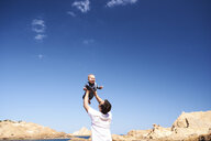 Spain, Menorca, father playing with little son on the beach - IGGF00901