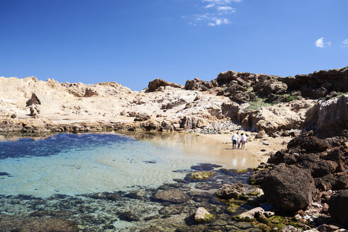 Wide shot of a family relaxing at the beach with son. Menorca, Spain. - IGGF00904