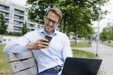 Young businessman sitting on park bench, using smartphone and laptop - KNSF05572