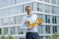 Young businessman holding smile sign - KNSF05578