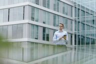 Young businessman standing in front of modern office building, usind digital tablet - KNSF05581