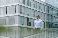 Young businessman standing in front of modern office building, watching soap bubbles - KNSF05584