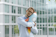 Young businessman standing in front of modern office building, hugging toy rocket - KNSF05587