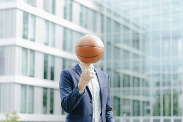 Young businessman standing in front of modern office building, balancing ball on his finger - KNSF05590