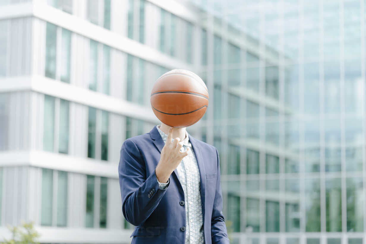 Young businessman standing in front of modern office building, balancing ball on his finger - KNSF05590 - Kniel Synnatzschke/Westend61