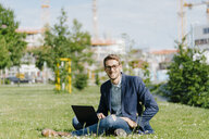 Young businessman sitting in park, using laptop - KNSF05593