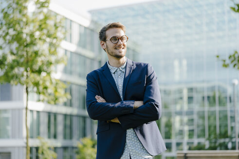 Young businessman standing in front of modern office building, with arms crossed - KNSF05596